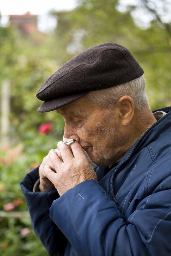 Vieil homme soufflant son nez images stock