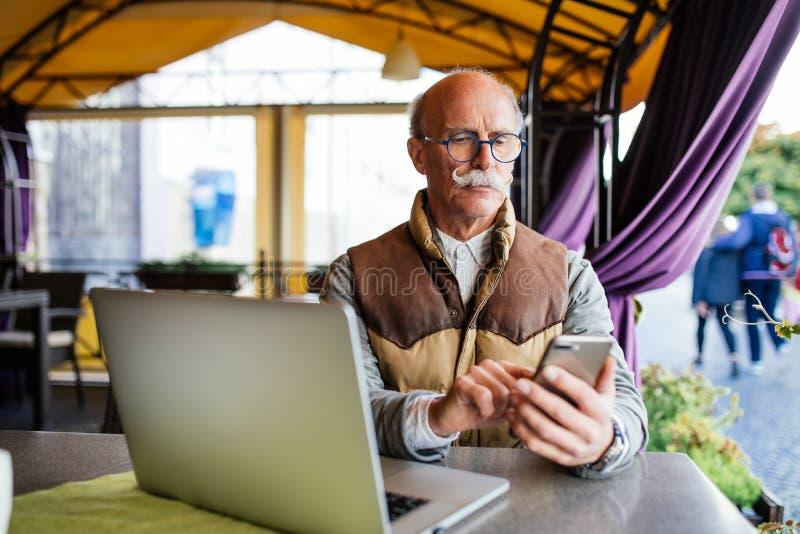 Vieil homme supérieur dans le costume et lien avec l'ordinateur portable et le smartphone, se reposant dans la maison de café de  images libres de droits