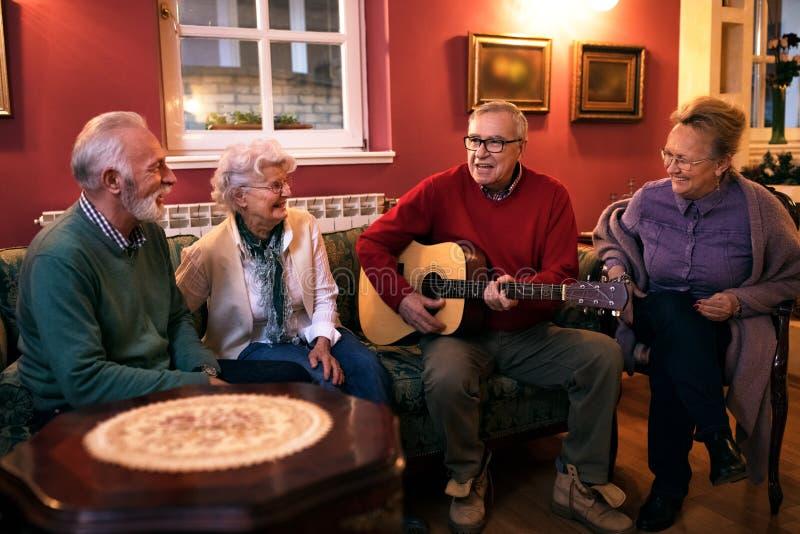 Vieil homme supérieur jouant la guitare avec ses amis, faisant le grand pair images libres de droits