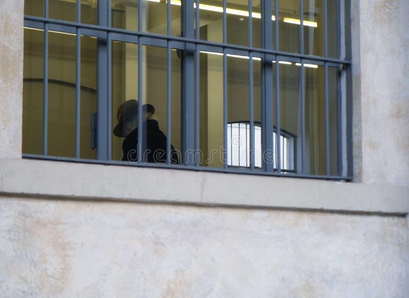 Vieil homme supérieur triste avec le chapeau à l'intérieur du bâtiment avec les fenêtres barrées - concept de loi et de justice photographie stock