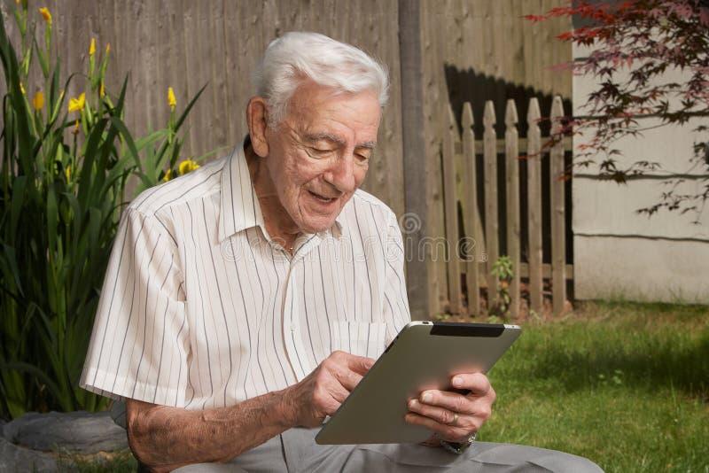 Vieil homme sur l'ordinateur de tablette photo stock
