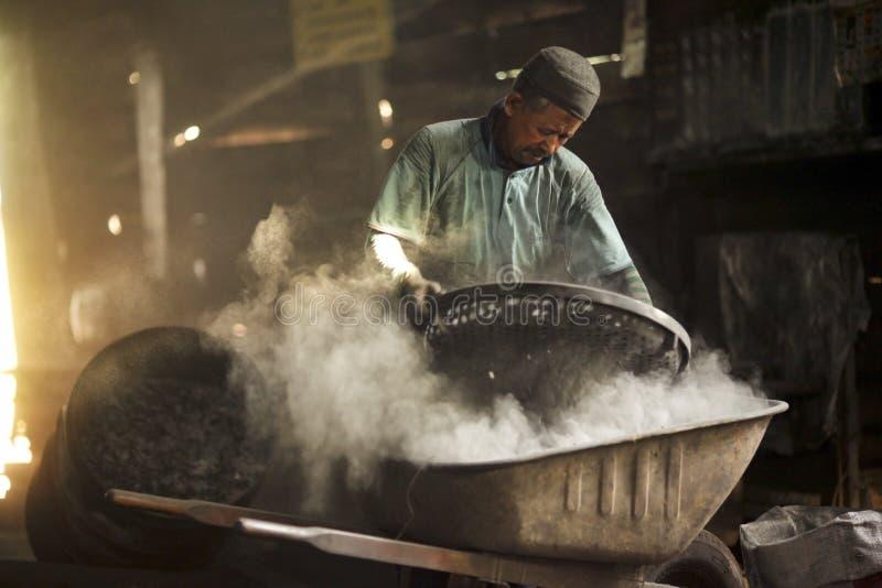 Vieil homme travaillant dans poussiéreux à l'usine de charbon de bois images libres de droits