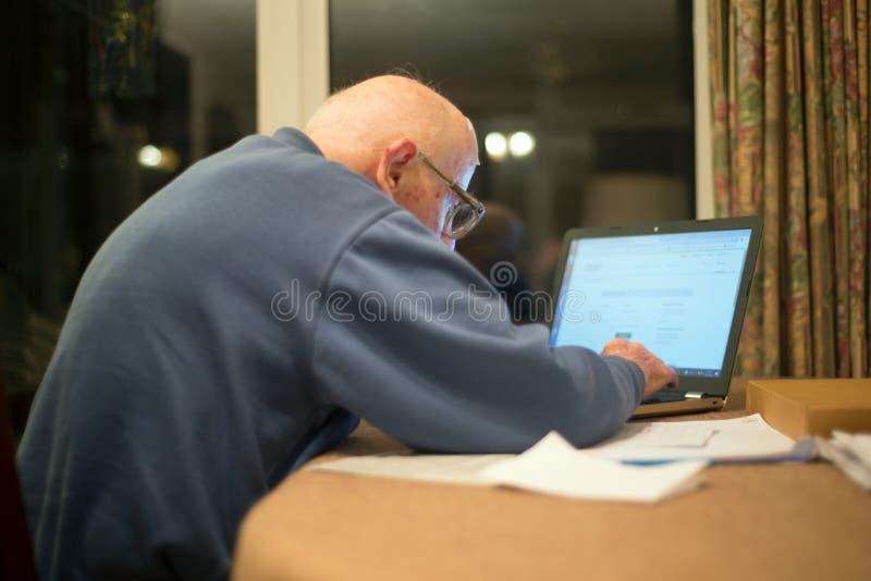 Vieil homme utilisant un ordinateur portable pour v?rifier ses portefeuilles d'actions, Hampshire, Angleterre, U k photos libres de droits
