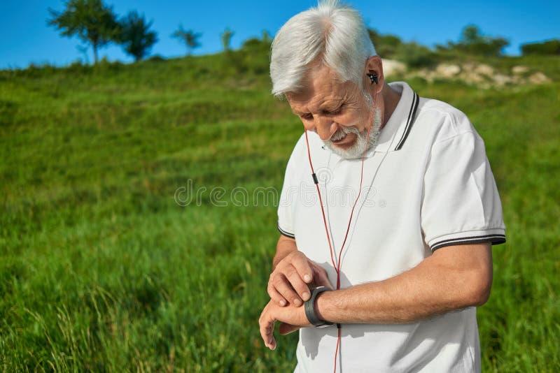 Vieil homme vérifiant le temps pendant les activités de sport d'extérieur image stock