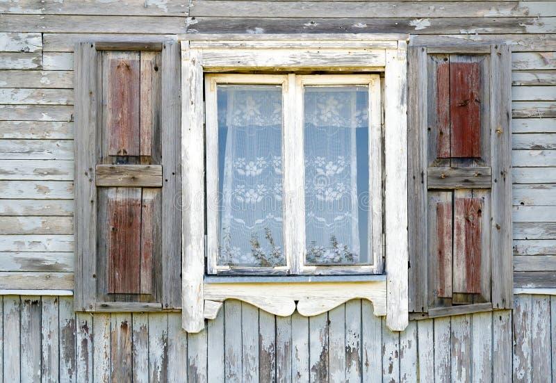 Vieil hublot blanc modifié dans la vieille maison en bois images libres de droits