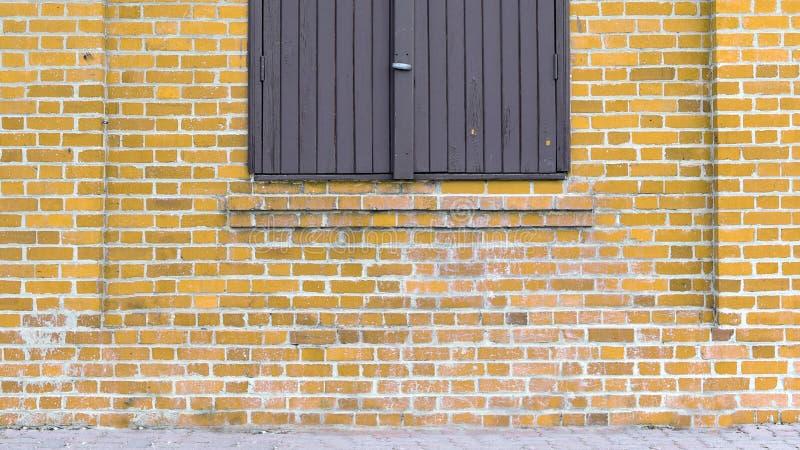 Vieil immeuble de brique jaune avec la fenêtre à volets images libres de droits