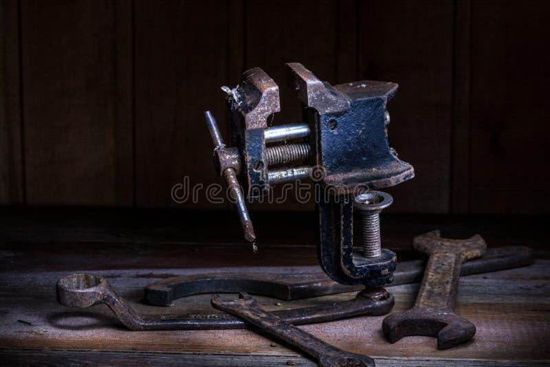 Vieil outil rouillé dans la chambre noire, endroit totalement sombre, jouant avec des lumières, vieille substance, vice, clés sur photos libres de droits