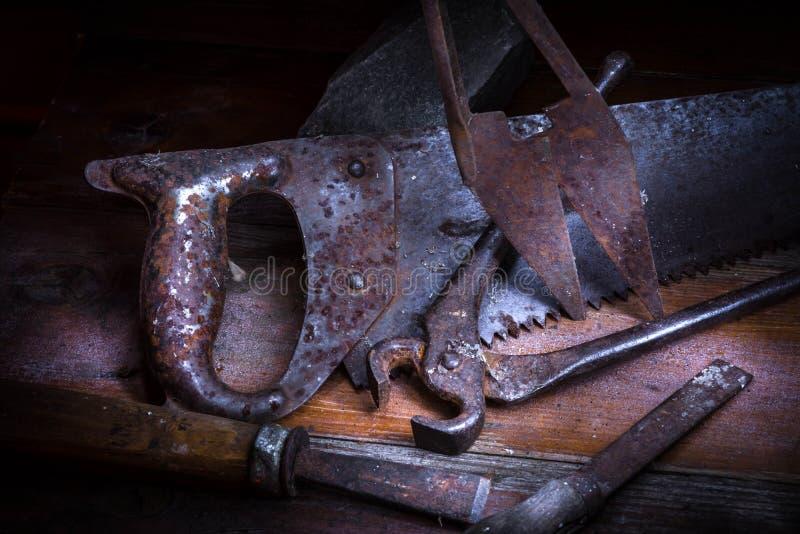Vieil outil rouillé dans la chambre noire, endroit totalement sombre, jouant avec des lumières, vieille substance, vice, clés sur photos stock