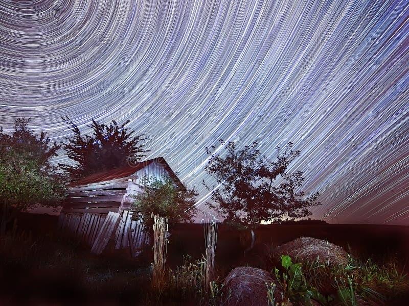 Vieil s'effondrer hayboal, meules de foin et voies des étoiles dans le ciel Cercles du mouvement des étoiles dans la photo de sky photos libres de droits