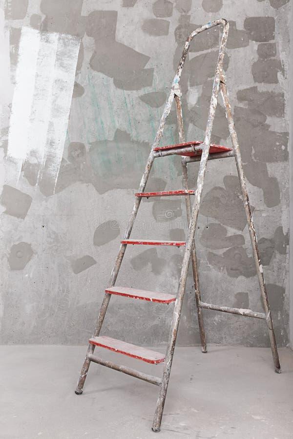 Vieille échelle peinte de stuc sur le fond de mur en béton photo libre de droits