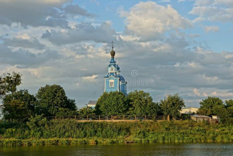 Vieille église en bois bleue en végétation verte sur le rivage du réservoir contre le ciel et les nuages photographie stock