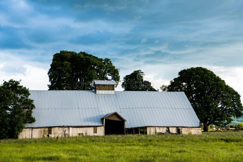 Vieille, abandonnée grange réglée dans un domaine vert sous un ciel foncé et orageux sinistre images stock
