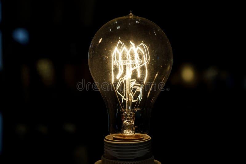 Vieille ampoule rougeoyant dans l'obscurité Fin vers le haut photos stock
