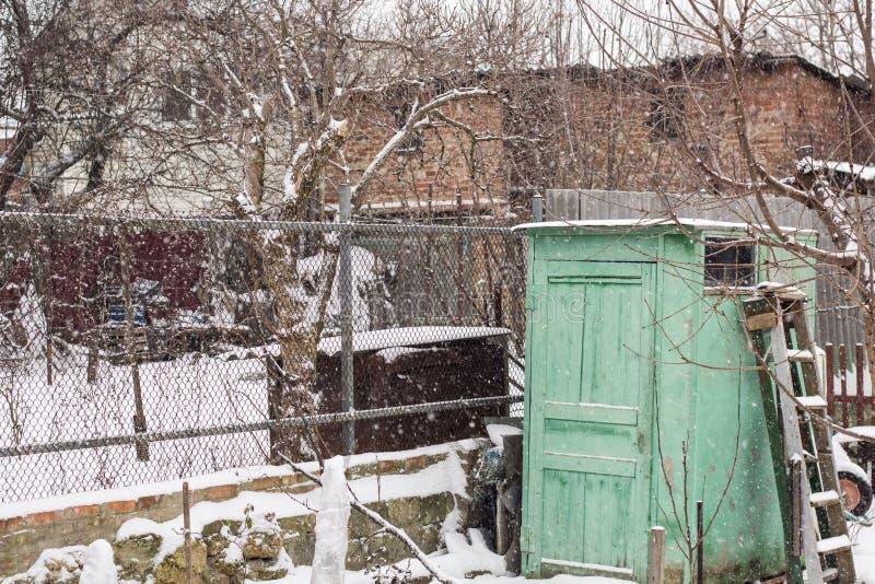 Vieille barrière couverte de neige devant une vieille maison, scène givrée d'hiver images libres de droits