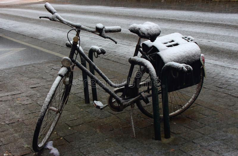 Vieille bicyclette de stationnement sous la neige à la rue Vélo abandonné photos libres de droits