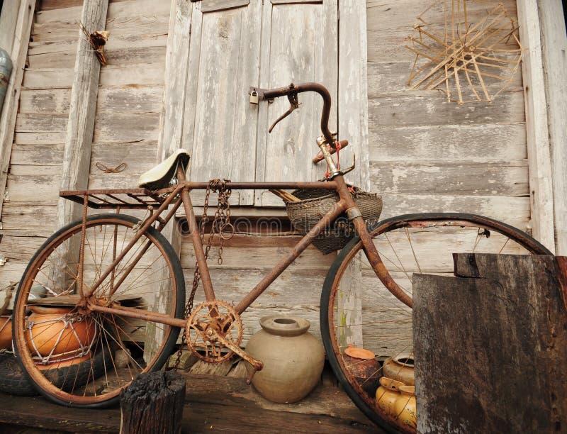 Vieille bicyclette et vieille maison en bois photographie stock
