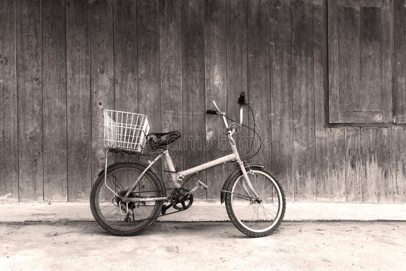 Vieille bicyclette noire et blanche se penchant contre le mur images libres de droits