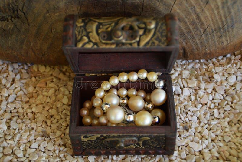 Vieille boîte à bijoux ornementale et un collier blanc de perle, une valise avec un trésor d'en haut photos libres de droits