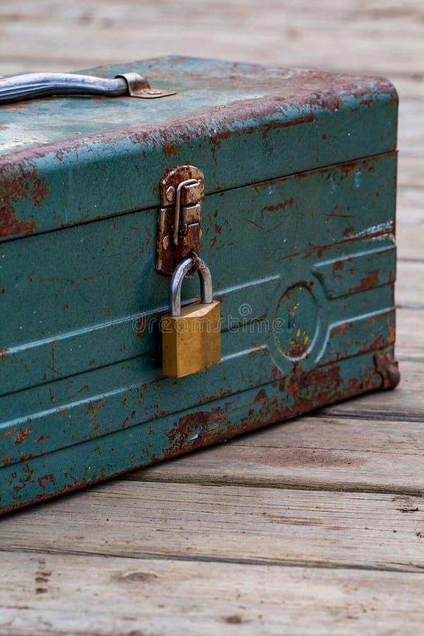 Vieille boîte à outils rouillée verrouillée vers le haut de se reposer sur un bois photographie stock