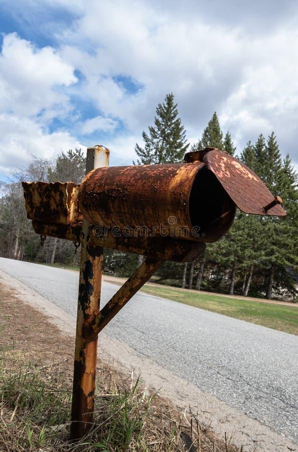 Vieille boîte aux lettres rouillée en métal sur une route de campagne photo stock