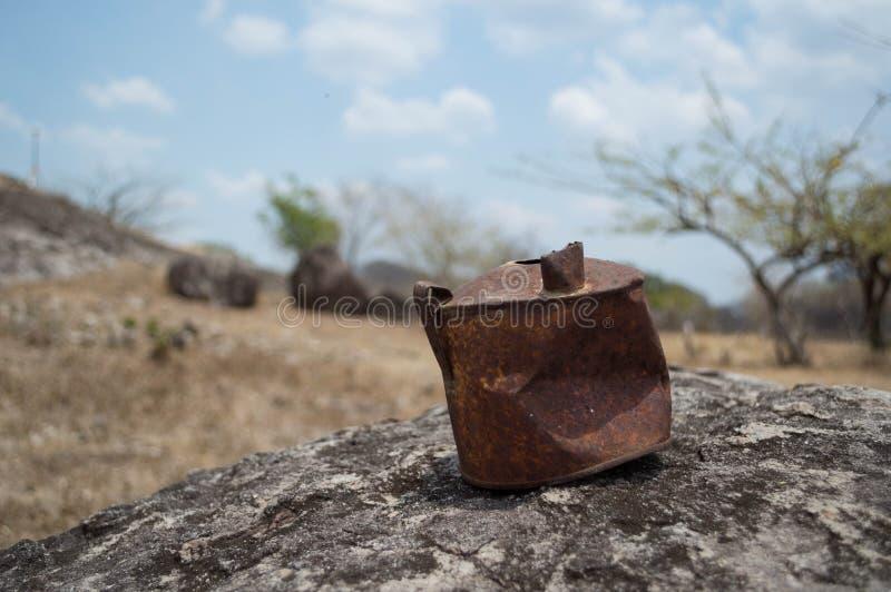 Vieille boîte rouillée sur une roche dans un désert images stock