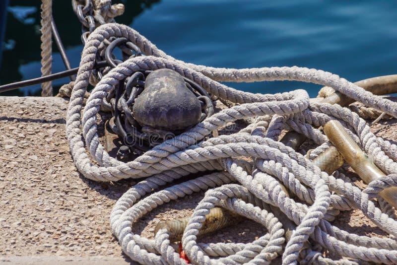 Vieille borne de amarrage rouillée avec les cordes nautiques nouées image libre de droits