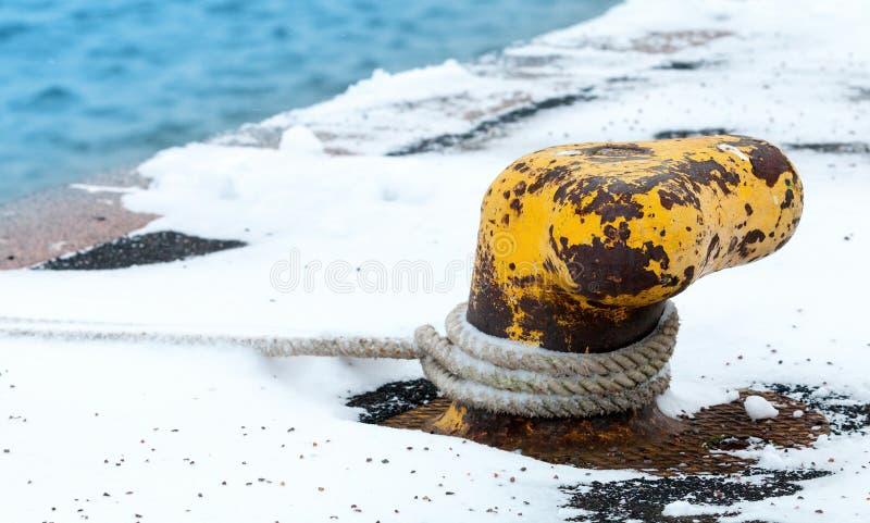 Vieille borne jaune rouillée d'amarrage avec la corde images libres de droits