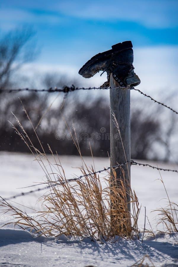 Vieille botte sur la barrière Post dans la neige images stock