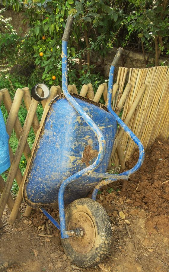 Vieille brouette bleue sur la roue de jardin image libre de droits