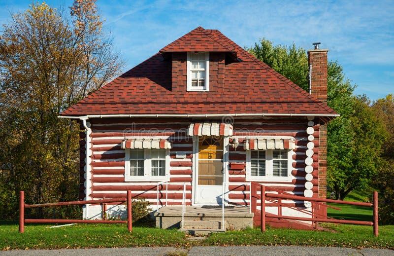 Vieille cabane en rondins avec le toit rouge de bardeau image libre de droits