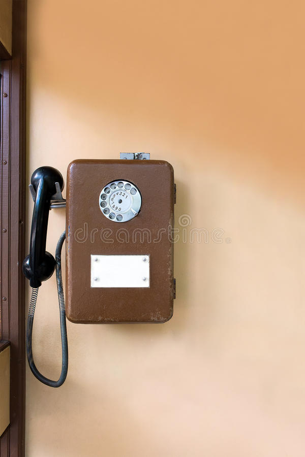 Vieille cabine téléphonique publique sur le mur Téléphone en métal de Brown images libres de droits