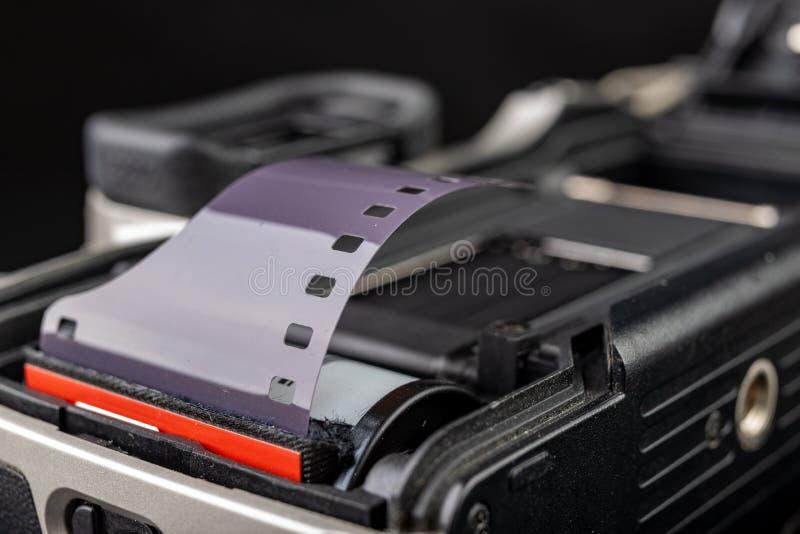 Vieille cam?ra analogue et nouveau film noir et blanc Accessoires pour la photographie analogue sur une table fonc?e image libre de droits