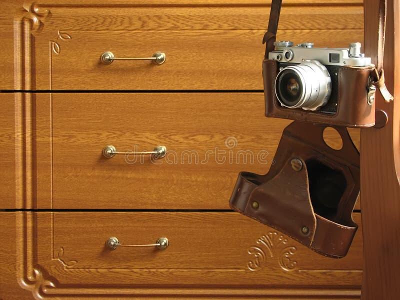 Vieille caméra de photo sur le fond de commode de chêne avec des cadres photos stock