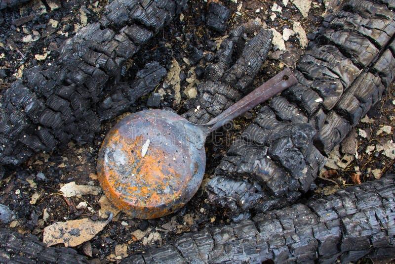 Vieille casserole et parties en bois carbonisées d'une maison brûlée dans la campagne photos stock
