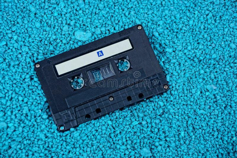 Vieille cassette sonore noire sur de petites pierres bleues photographie stock libre de droits