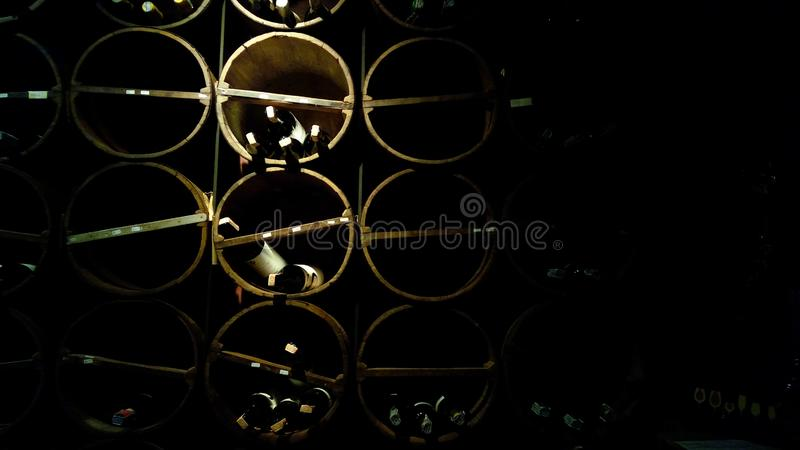 Vieille cave Salle d'entreposage avec des bouteilles de vin rouge et blanc étendues à l'intérieur des barils en bois de chêne photo stock