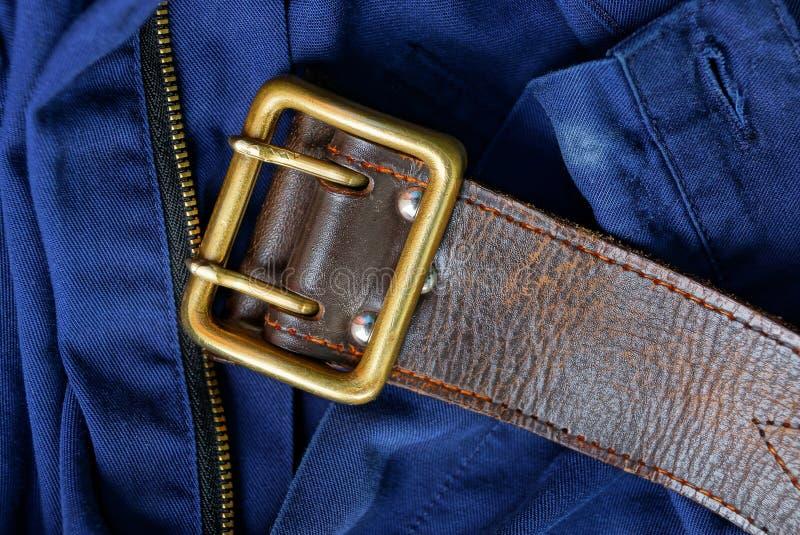 Vieille ceinture en cuir brune avec la boucle en laiton sur le pantalon bleu image libre de droits