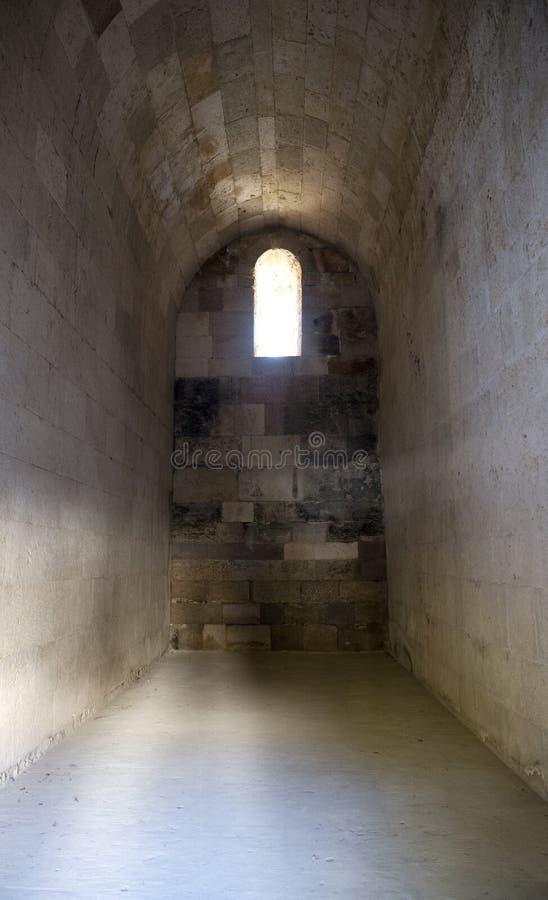 Vieille cellule antique de Dungeon de pierre de château avec l'hublot images libres de droits