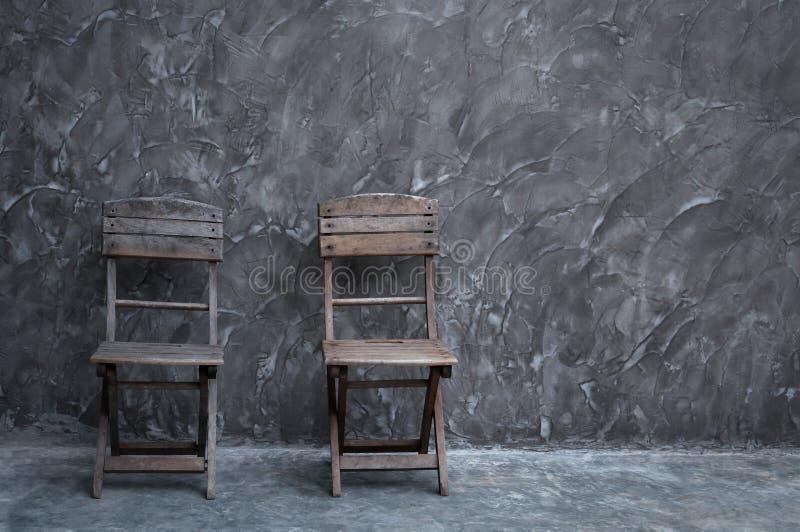 Vieille chaise de vintage en bois au mur en béton foncé image libre de droits