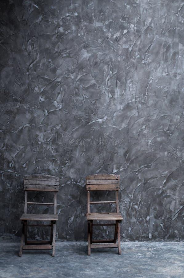 Vieille chaise de vintage en bois au mur en béton foncé images libres de droits