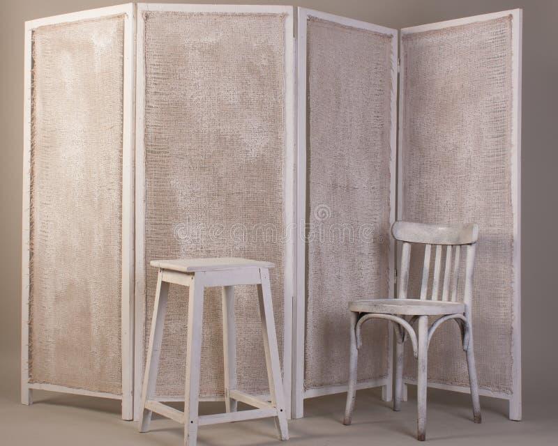 Vieille chaise en bois blanche, chaise et écran se pliant se pliant d'isolement sur le gris photos libres de droits