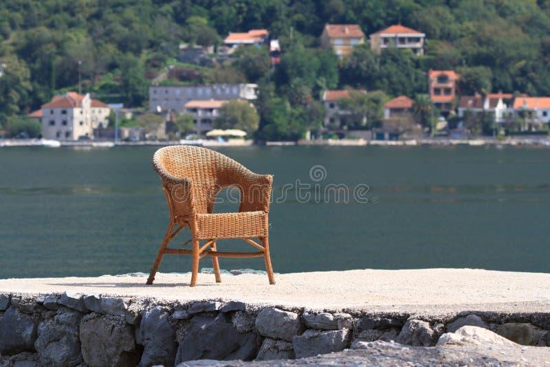 Vieille chaise en osier de rotin sur le bord de mer photos stock