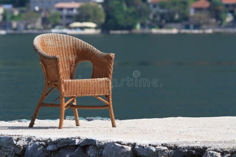 Vieille chaise en osier sur un fond d'un golfe de mer image libre de droits