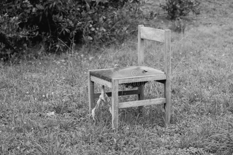 Vieille chaise sur l'herbe, photo noire et blanche photographie stock libre de droits