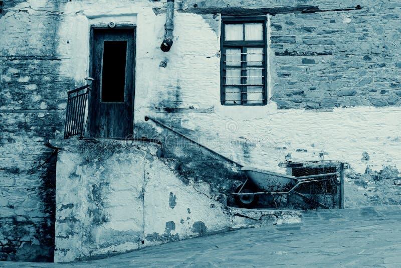 Vieille Chambre en pierre avec la porte et la fenêtre en bois, escalier, Rusty Gutter et brouette i cyan photos stock