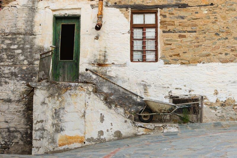 Vieille Chambre en pierre avec la porte et la fenêtre, l'escalier, le Rusty Gutter et la brouette photo libre de droits