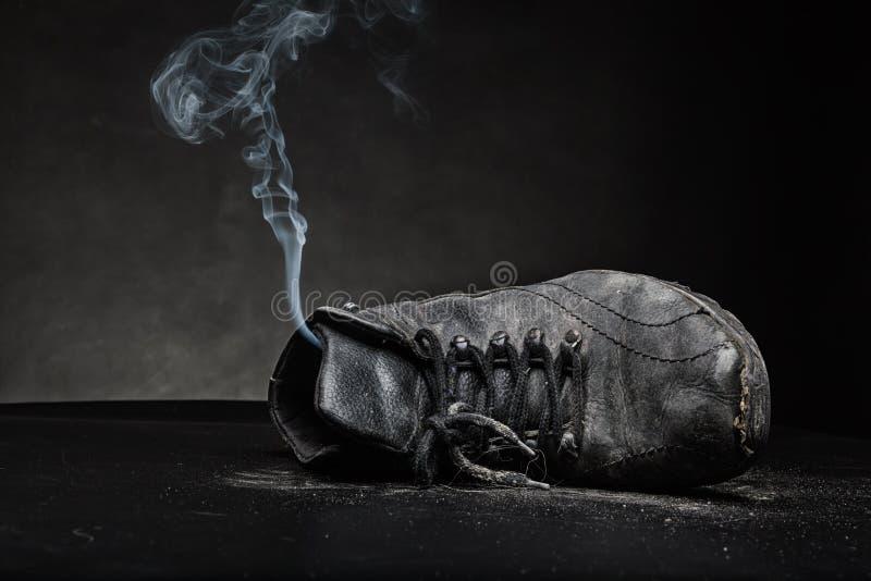 Vieille chaussure de travail dans la fumée photos stock