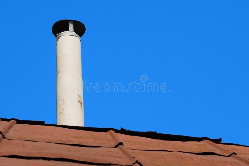 Vieille cheminée de tuyau d'amiante au-dessus d'un toit rouillé en métal image stock