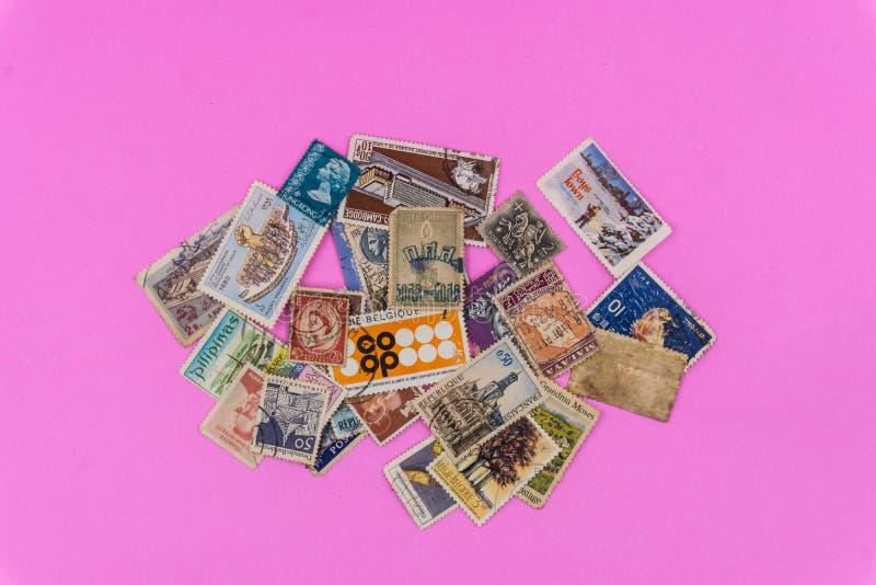 Vieille collection de timbres multi de nation sur le fond rose photo stock