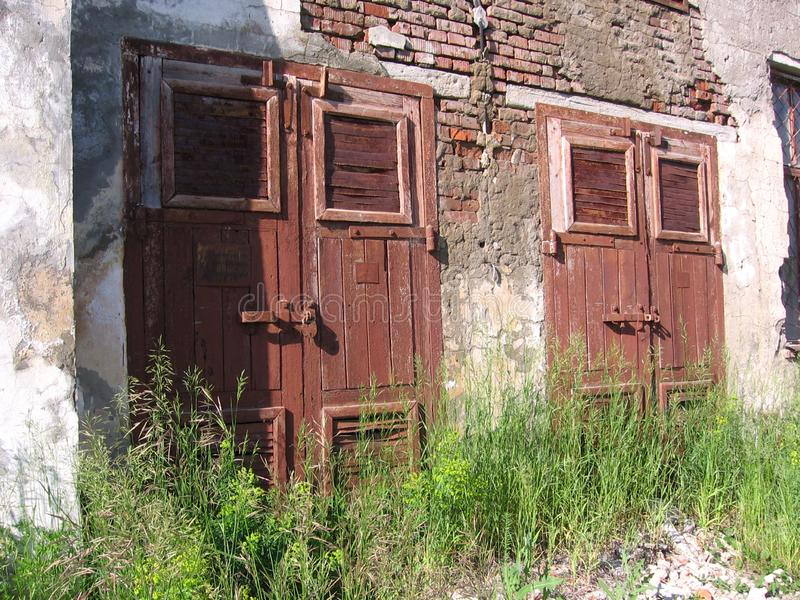 Vieille construction inutile abandonnée de bâtiment sombre de porte fermée photos libres de droits